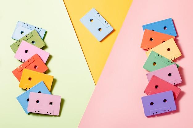 Cassetes áudio pintadas no fundo multicolorido brilhante, espaço da cópia, vista superior. fundo musical retrô