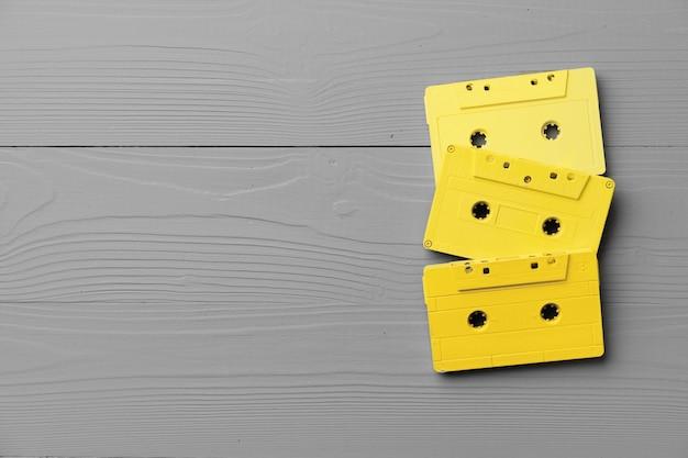 Cassetes de áudio amarelas na vista superior cinza, espaço de cópia