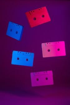 Cassetes de áudio coloridas penduradas no ar contra roxo