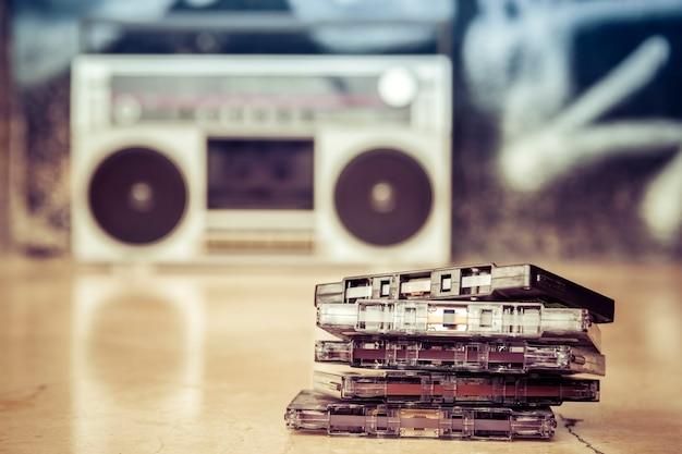 Cassetes de áudio empilhados e colocados no chão com um velho boombox