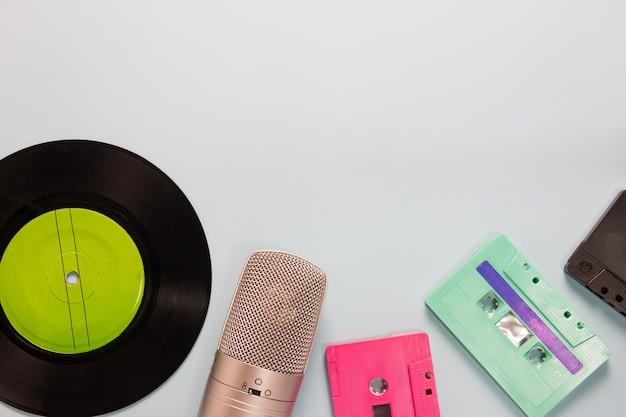 Cassetes de áudio, microfone e gravador com espaço para texto