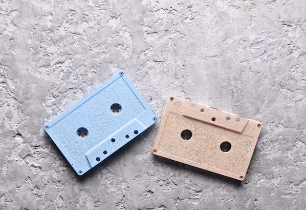 Cassetes de áudio pastel azuis e rosa em um fundo cinza de concreto