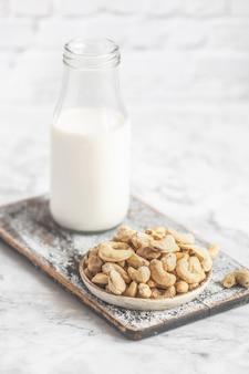 Castanha de caju crua na mesa e garrafa de leite
