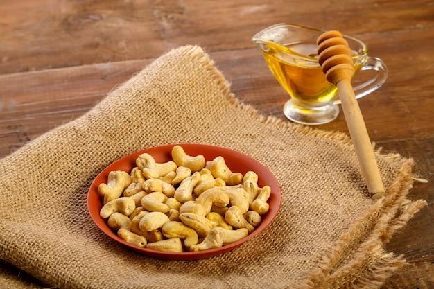 Castanha de caju em um prato sobre serapilheira ao lado do mel com uma colher em uma mesa de madeira foto horizontal