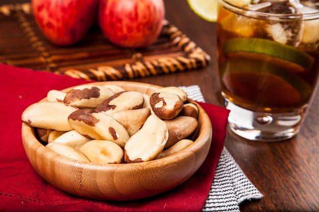 Castanha do brasil em uma mesa de madeira com maçãs e chá gelado no fundo.