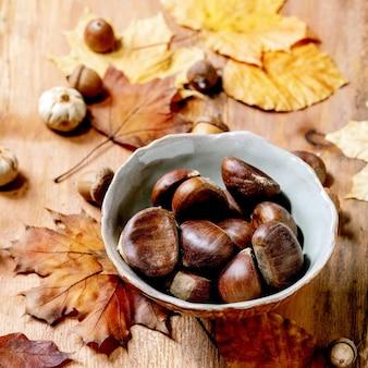 Castanhas comestíveis e folhas de outono