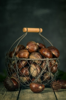 Castanhas cruas em uma madeira em uma cesta de ferro.