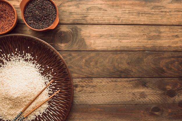 Castanho; vermelho; e grãos de arroz branco na mesa de madeira