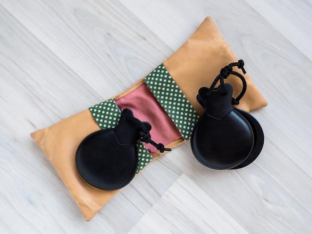 Castanholas pretas e uma caixa de couro marrom estão no chão