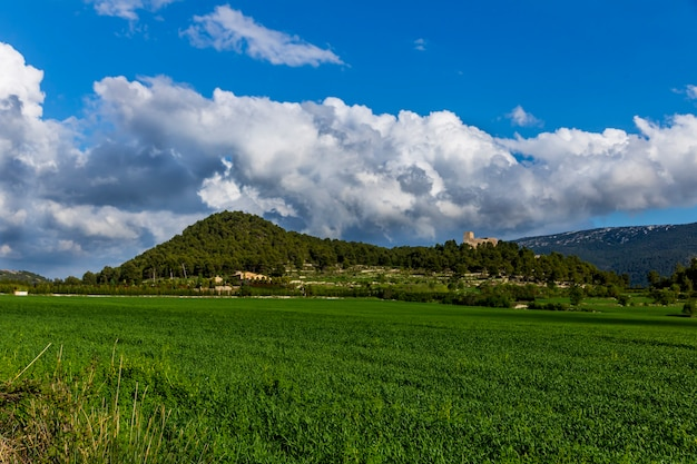Castelo barxell em um prado verde em um dia com nuvens brancas e cinza e raios de sol com montanhas ao fundo.
