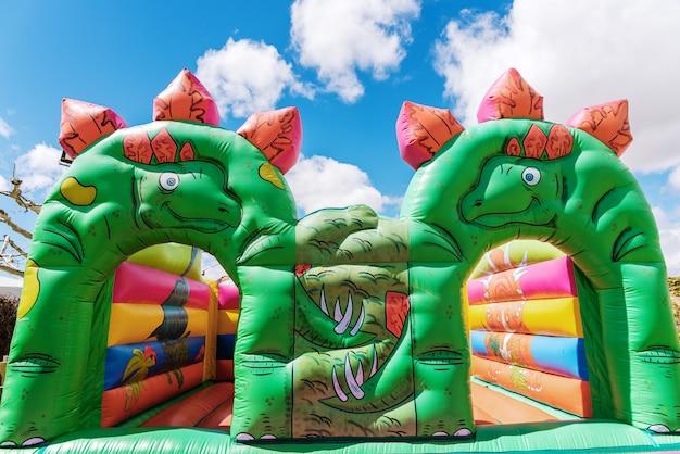 Castelo bouncy na forma dos dinossauros em um campo de jogos das crianças ao ar livre.