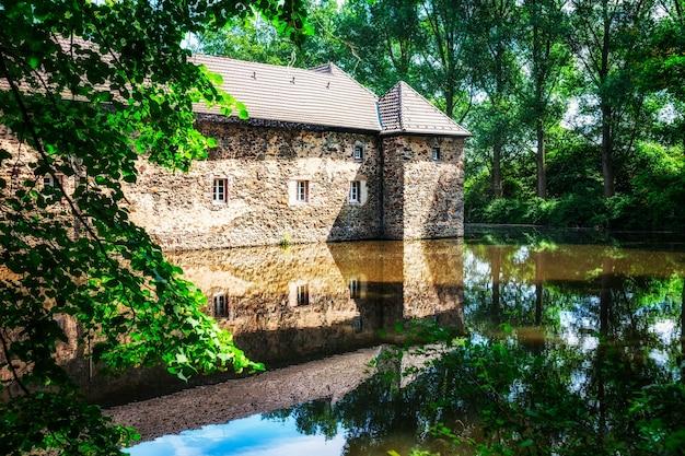 Castelo de água com reflexo na lagoa. casa medieval graven, alemanha