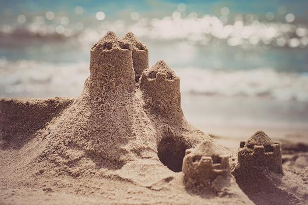 Castelo de areia em pé na praia. conceito de férias de viagens.