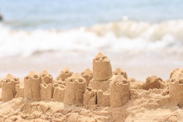 Castelo de areia em pé na praia.