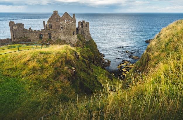 Castelo de dunluce no penhasco. linha costeira irlandesa.