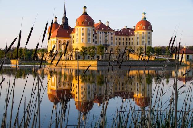 Castelo de moritzburg refletido na água ao pôr do sol na saxônia, alemanha