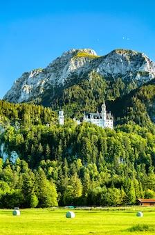 Castelo de neuschwanstein com parapentes no céu e fardos de feno em um campo abaixo. alpes da baviera, alemanha