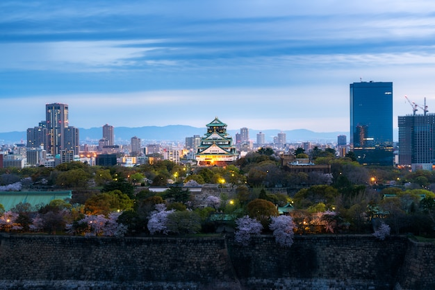 Castelo de osaka com flor de cerejeira e distrito financeiro em osaka, japão.