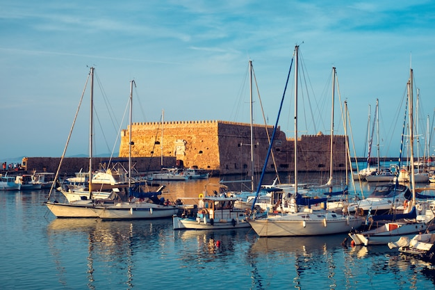 Castelo do forte veneziano em heraklion e barcos de pesca ancorados, ilha de creta, grécia no pôr do sol
