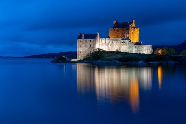Castelo eilean donan nas montanhas escocesas com reflexo de água fotografado na hora azul após o pôr do sol
