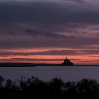 Castelo em frente ao oceano sob um céu nublado durante o pôr do sol