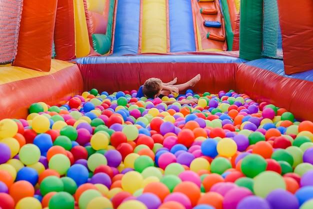 Castelo insuflável cheio de bolas coloridas para as crianças saltarem