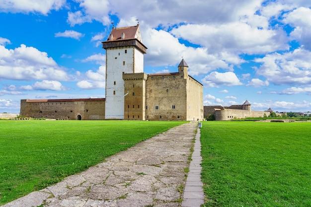 Castelo medieval de narva com suas paredes de pedra e sua estrada de acesso no prado verde.