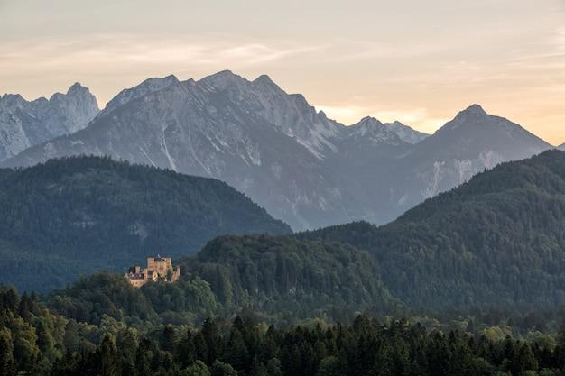 Castelo no verão de paisagem de fantasia com pôr do sol