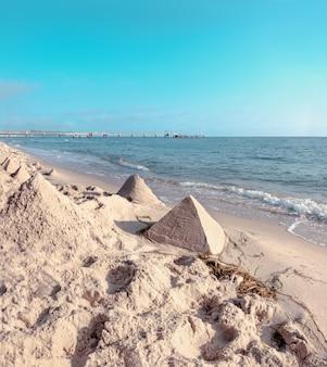 Castelos de areia em forma de pirâmides em uma praia no mar báltico