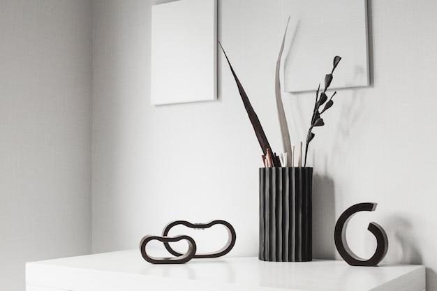 Castiçais de madeira escuros e vaso no interior branco