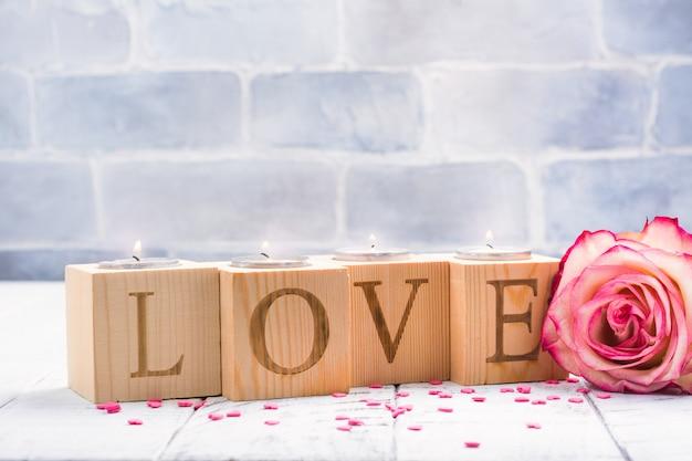 Castiçais de madeira românticos com punhos de chá ardentes. cartão de dia dos namorados