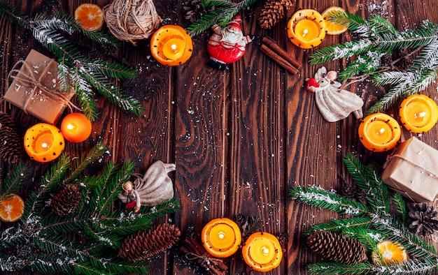 Castiçais feitos de mandarinas com ramos de abeto, brinquedos e presentes na mesa de madeira. natal e ano novo