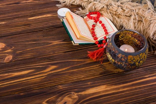 Castiçal aceso; kuran e vermelho grânulos de oração na mesa de madeira