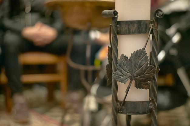 Castiçal de ferro forjado feito à mão usado dentro de uma igreja católica durante um batismo.