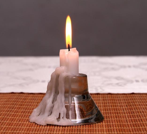 Castiçal para uma vela. vela acesa derretida em um fundo branco-acinzentado.