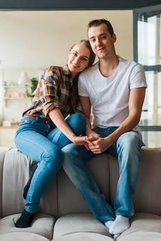 Casual casal apaixonado sentados juntos no sofá