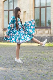 Casual e bonito. garota feliz marcha ao ar livre urbano. criança usa estilo casual. tendências de verão. guarda-roupa casual moderno. roupas infantis para o dia a dia. look casual e chique.