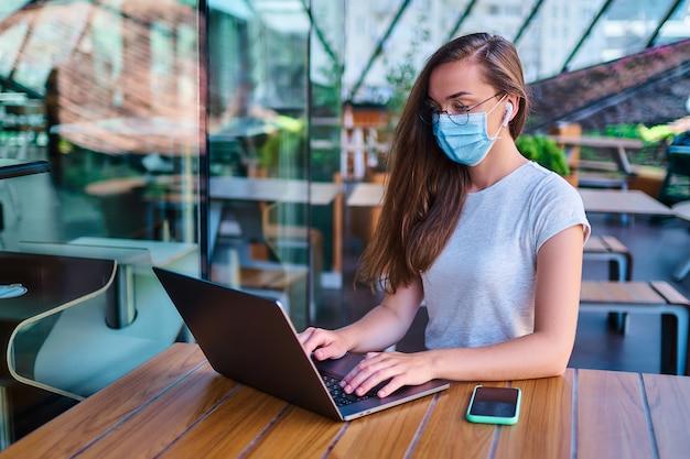 Casual freelancer mulher trabalhadora em máscara protetora, fones de ouvido sem fio brancos e óculos trabalha remotamente no computador no café. proteção da saúde em locais públicos