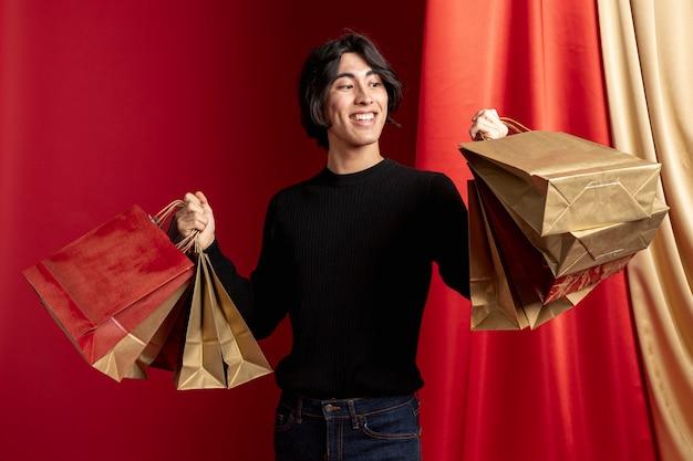 Casual homem segurando sacolas posando para o ano novo chinês