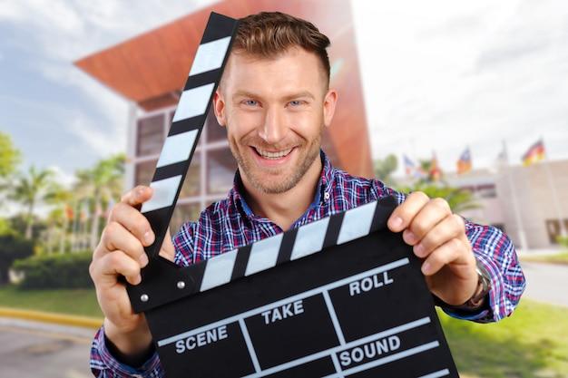 Casual homem segurando um aplauso de filme aberto