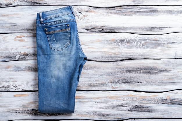 Casual jeans dobrado jeans em fundo de madeira, calças femininas de novo item de alta qualidade em coágulo.