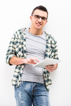 Casual jovem está segurando um touch pad tablet pc.