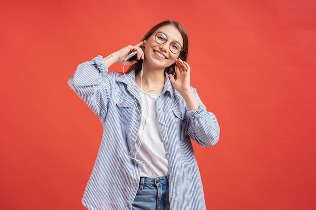 Casual jovem sorrindo com fones de ouvido e óculos na parede vermelha