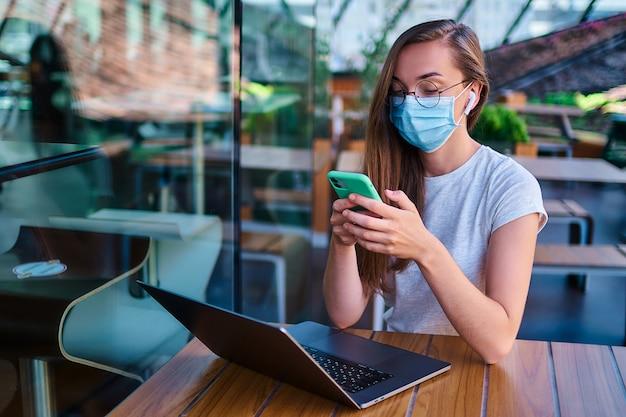Casual jovem trabalhadora freelancer em máscara facial, fones de ouvido sem fio brancos e óculos redondos usando telefone e computador para trabalhos remotos on-line no café