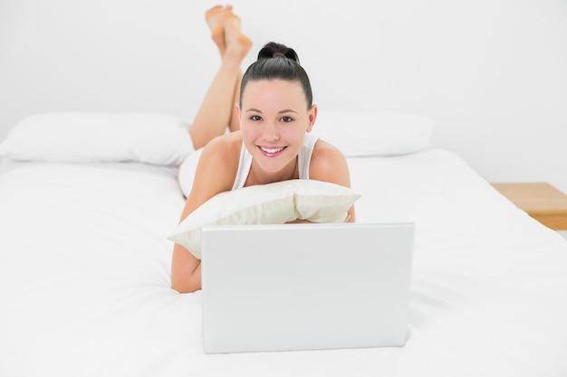 Casual mulher sorridente com laptop na cama
