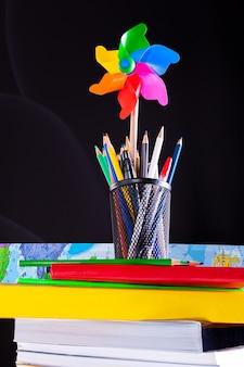 Cata-vento e pote de lápis em livros empilhados, material escolar em uma mesa branca com textura de quadro-negro no fundo. aprendizagem, conceito de educação