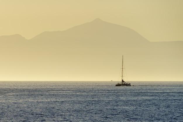 Catamarã navegando no mar azul com a silhueta de uma enorme ilha no horizonte, a ilha de tenerife com o vulcão teide ao fundo. espanha. europa.