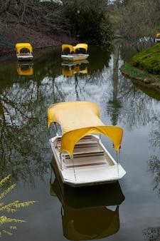 Catamarãs, barcos vazios sem pessoas, flutuando em um pequeno rio com água escura. solidão e saudade