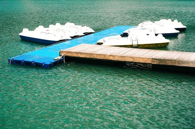 Catamarãs brancos ancorados na água azul. pedalinhos