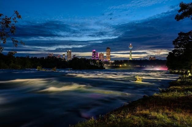 Cataratas do niágara e rio à noite sob luzes coloridas